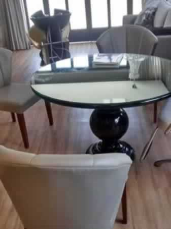 Itaúna - Mesa com tampo redondo de vidro  Com suporte/pé central de madeira na cor preta,